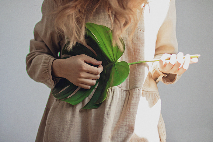 A close up portrait of a female model holding a large leaf as if it was a guitar she's playing