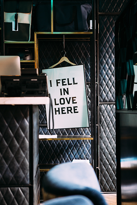 A sign reading 'I fell in love here' hanging in a wardrobe - valentines day photoshoot ideas