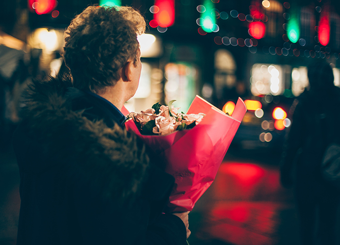 A street portrait of a man holding a bouquet of flowers - valentine day photography