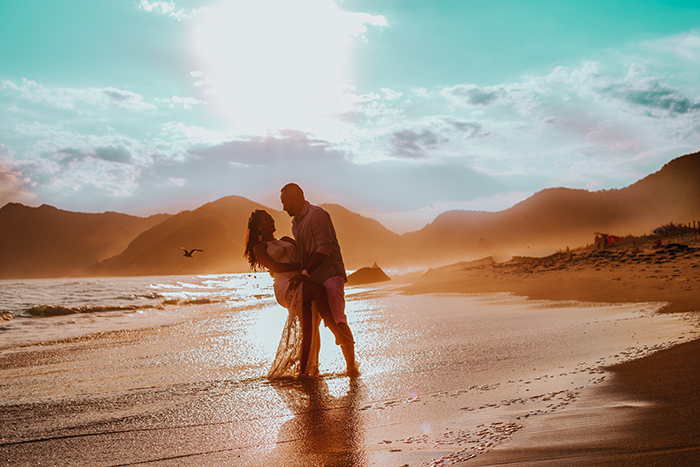 A stunning portrait of a couple posing on a beach at sunset - valentine photography