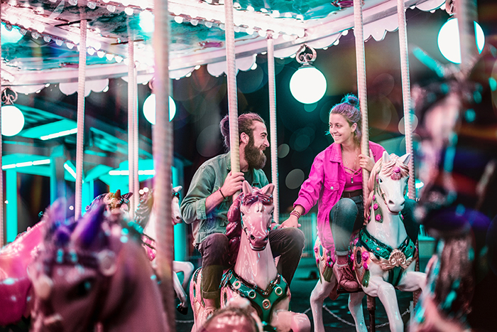 A couple posing on a carousel for a valentines day photoshoot