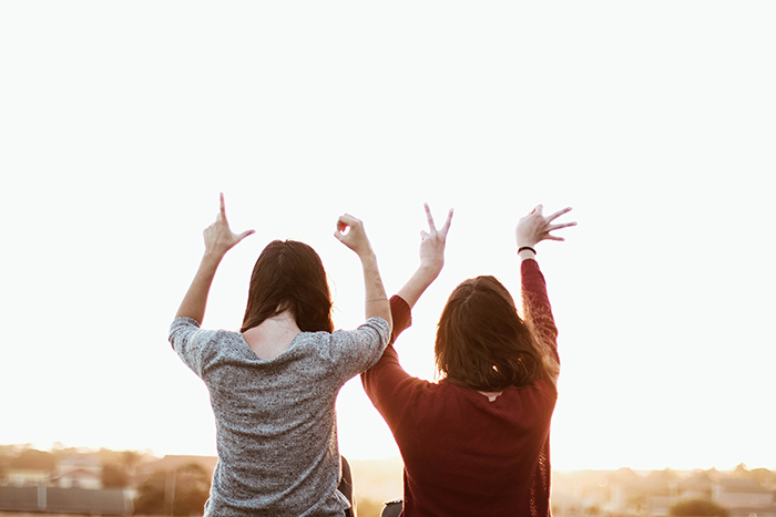 A valentines day photo of two friends holding their hands in the air