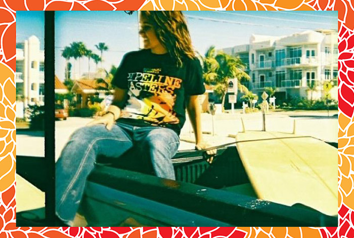 A portrait of a girl posing on the back of a convertible car, with an orange patterned Photoshop frame