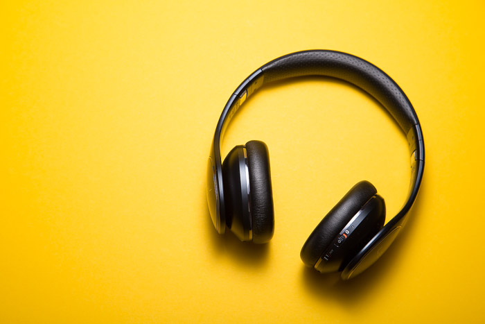 A product photography shot of headphones on yellow background