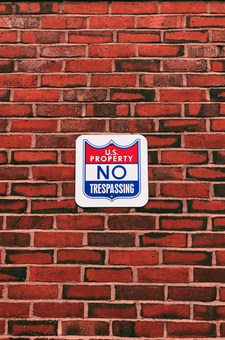 An image of a sign and brick wall
