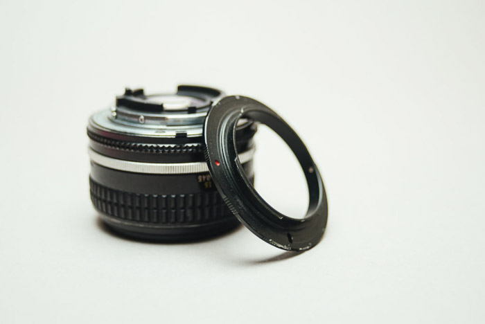 A camera lens beside a reversing ring on white background