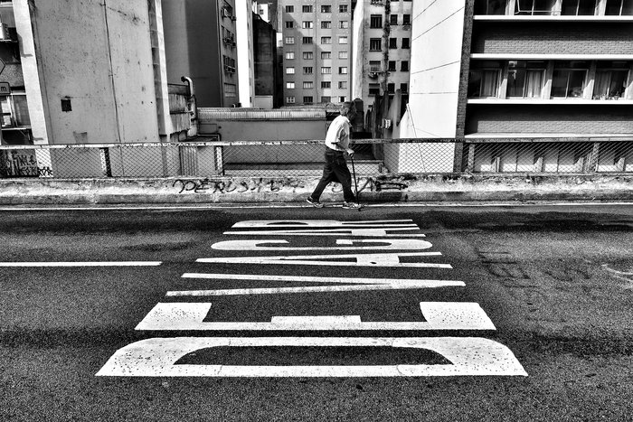 A black and white portrait of an old man walking down an urban street - street photography quotes