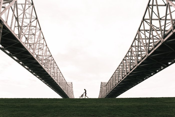 the silhouette of a woman and baby walking past two large steel bridges - susan sontag on photography quotes
