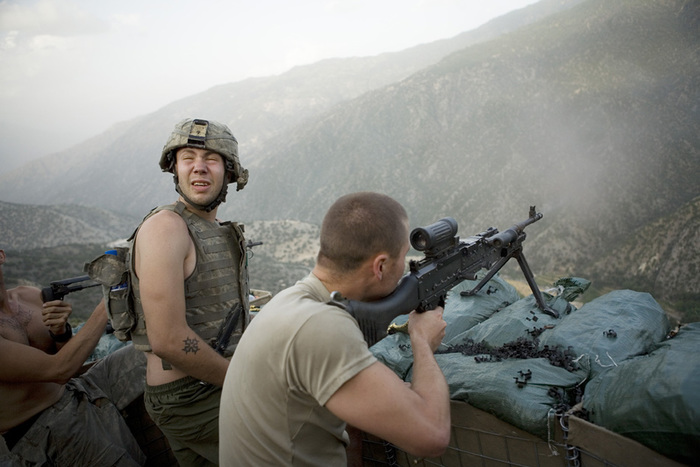 Soldiers aiming guns towards the mountains, war photography by Tim Hetherington