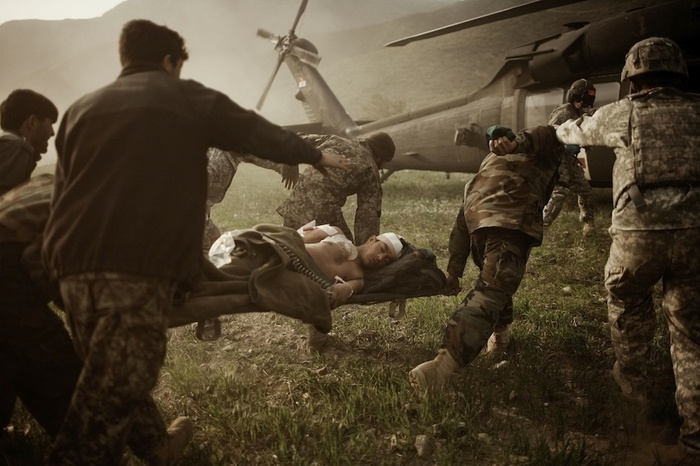 Soldiers helping injured people towards a helicopter by Moises Saman, best war photographers