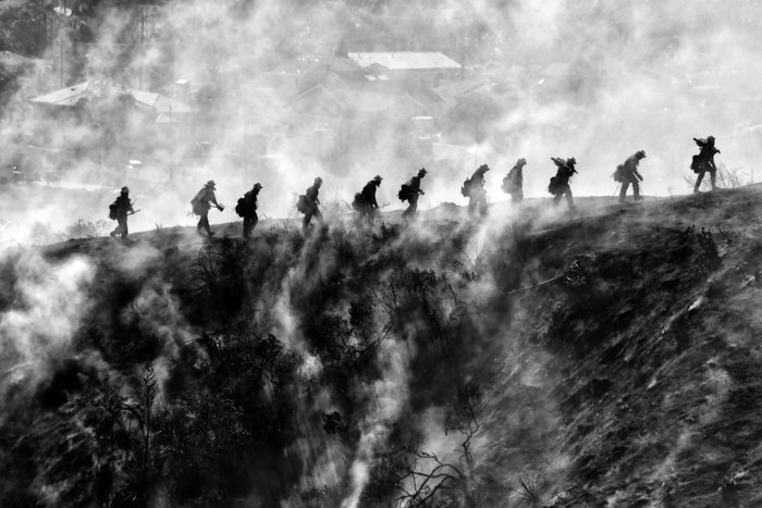 A black and white shot of soldiers walking through a landscape by war photographer Nick Ut