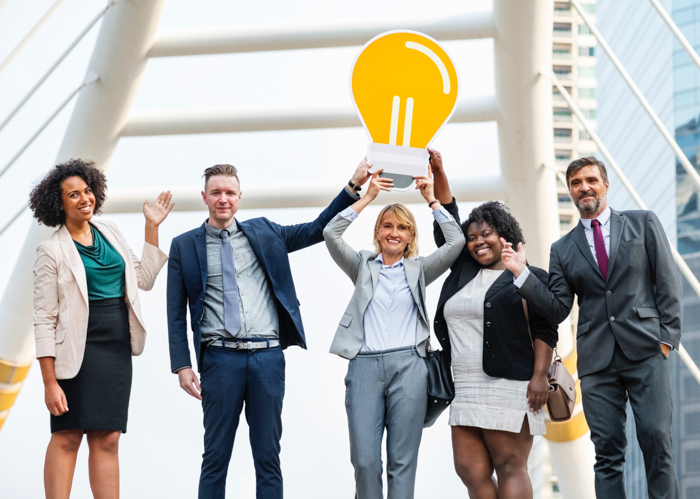 A group portrait of overly happy corporate office employees holding a cardboard lightbulb - business stock photos