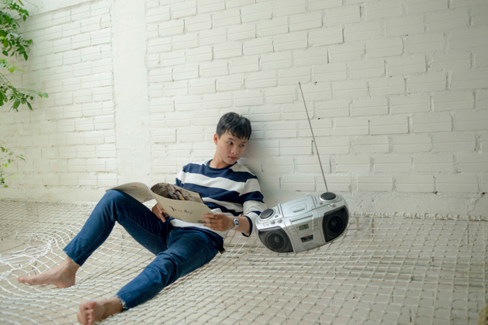 A badly edited stock photo of a man sitting beside a radio