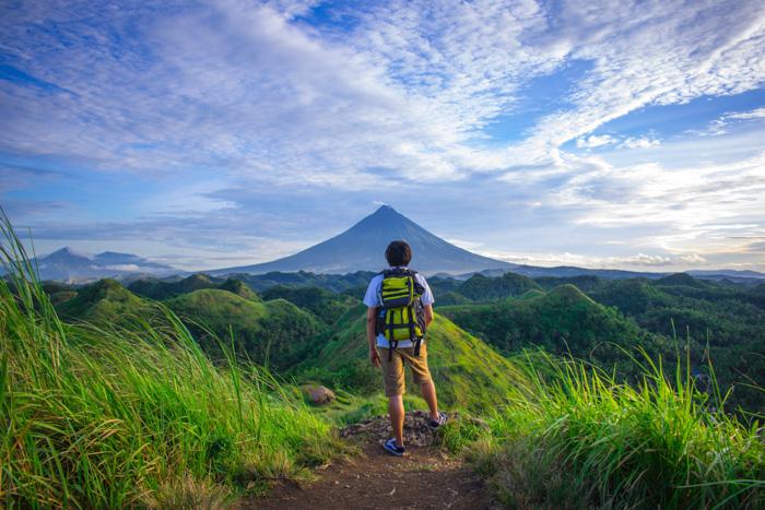 A portrait of a backpacker gazing onto a breathtaking mountainous landscape