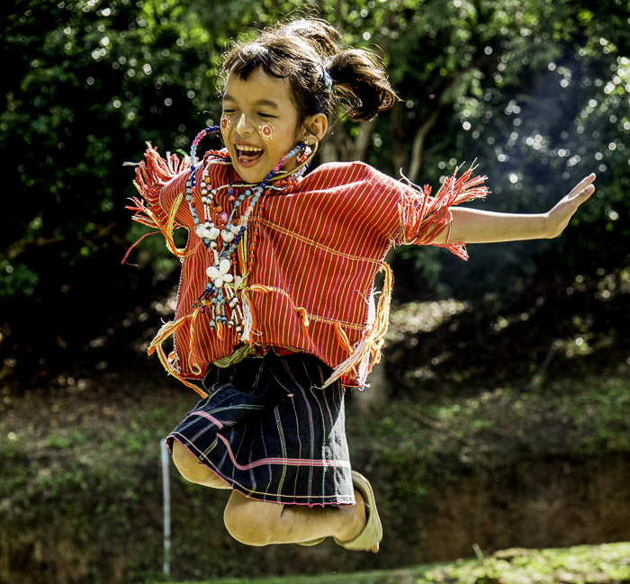 A portrait of a young child jumping with joy, shot using backlight photography