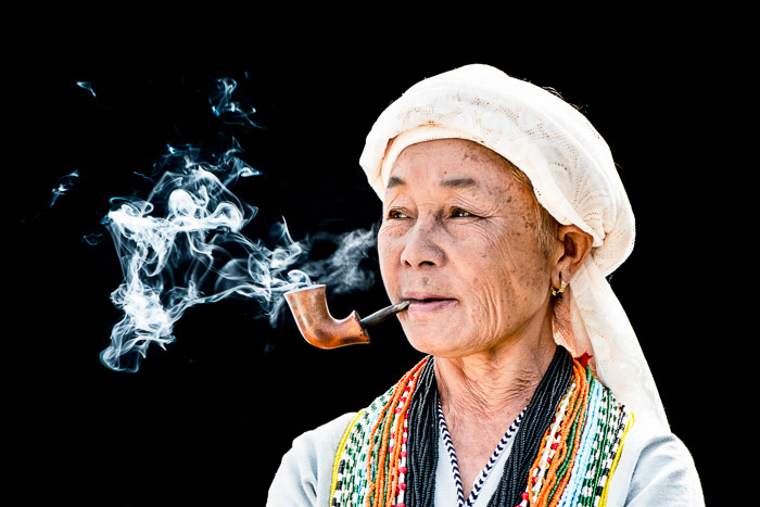 old asian woman smoking a pipe in colourful clothing with a black background