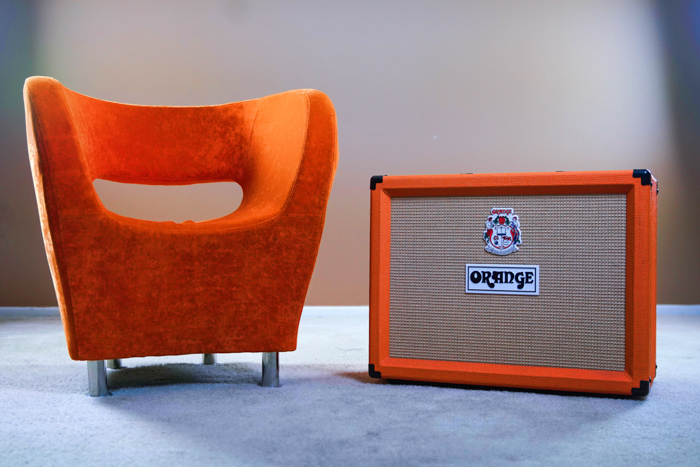 A product photography shot of an orange amp beside an orange chair - photography copyright