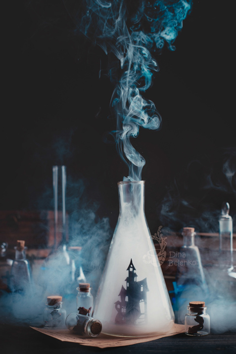 Atmospheric magic themed still life composition featuring glass bottles, smoke and test tubes