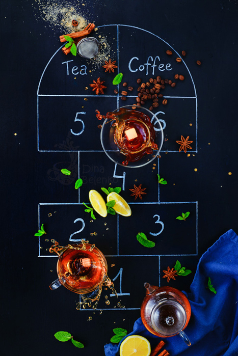 A flat lay photo of tea cups and ingredients on a chalk hopscotch grid on a dark background - creative still life composition
