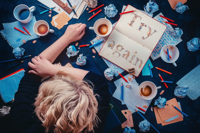 A photo of a child leaning on a table filled with coffee cups and stationary on a dark background - creative still life composition