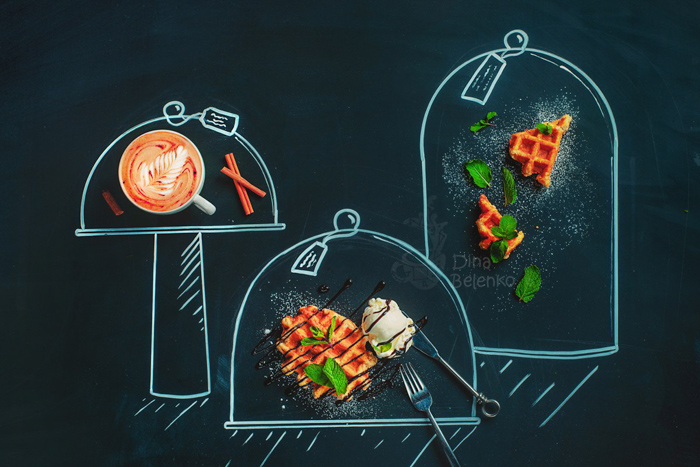A still life flat lay of coffee, waffles and ingredients on a chalk hopscotch grid on a dark background