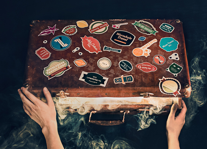 An overhead shot of a person opening an old suitcase covered with stickers - examples of using text in photography