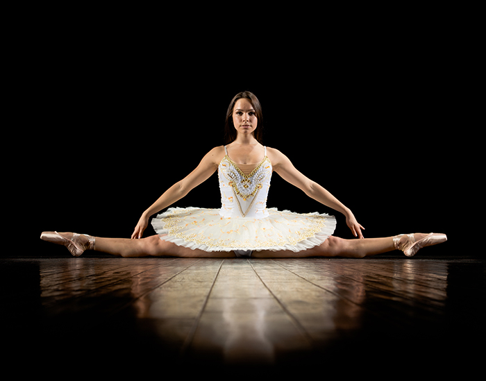 Artistic ballet photography shot of a female ballerina dancing onstage in low light