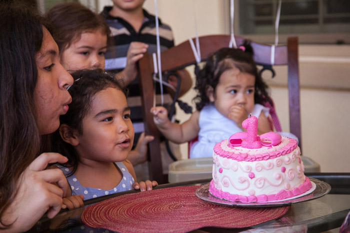 A little girl blowing out birthday candles on a cake at a family birthday party - birthday party photography
