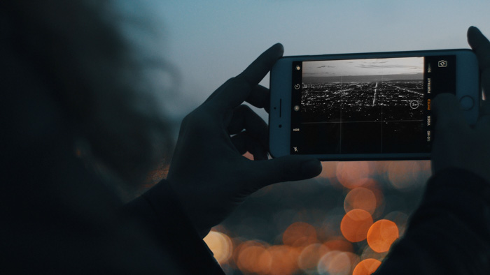 A person taking a photo of a stunning cityscape with a smartphone in low light - best black and white smartphone apps
