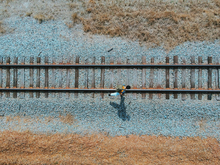 A birds eye view camera angle of a man walking along traintracks