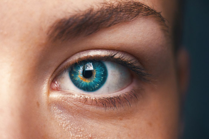 A close up photo of a female models blue eye