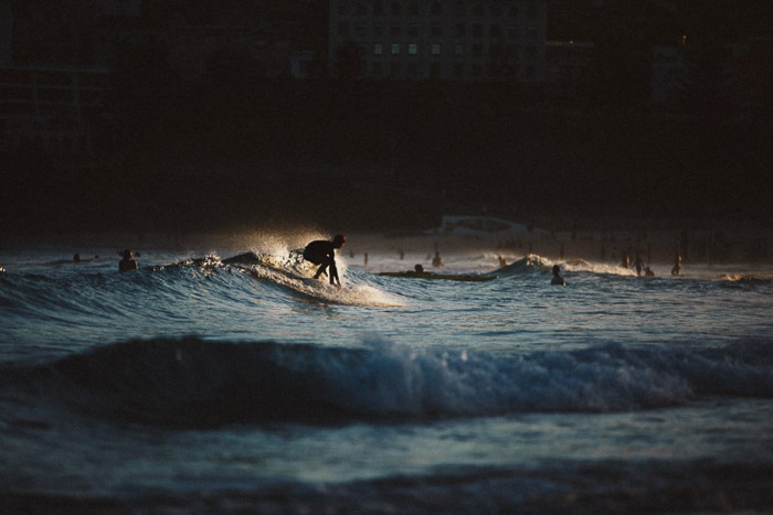 A person surfing in low light