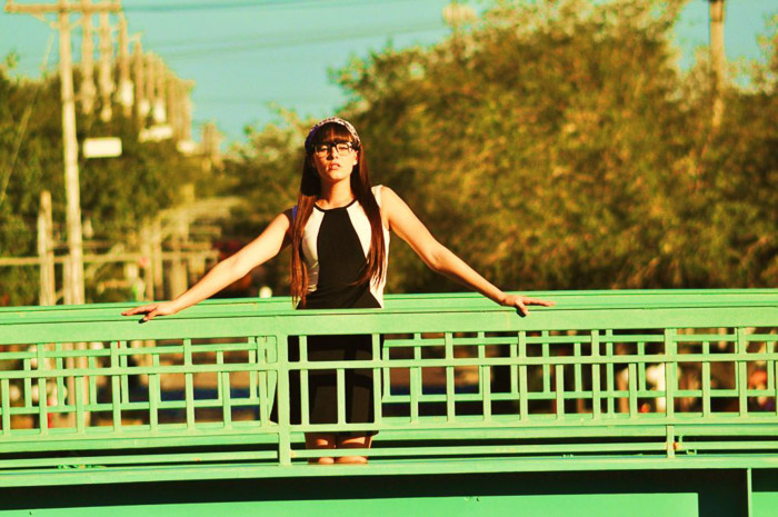 A portrait of a female model posing on a green bridge with long shot camera angles