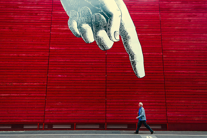A conceptual photography shot of a man walking under a huge picture of a pointing finger