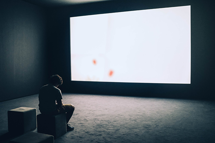 A conceptual self portrait of a man sitting in front of a large blank screen