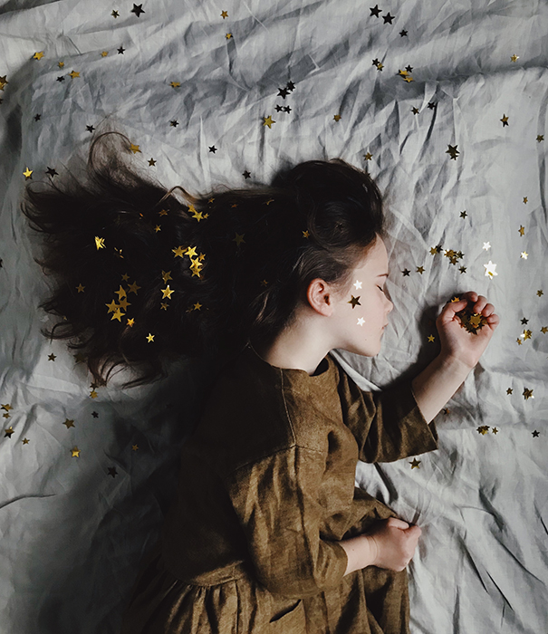 A dreamy conceptual portrait of a little girl sleeping, covered in golden stars