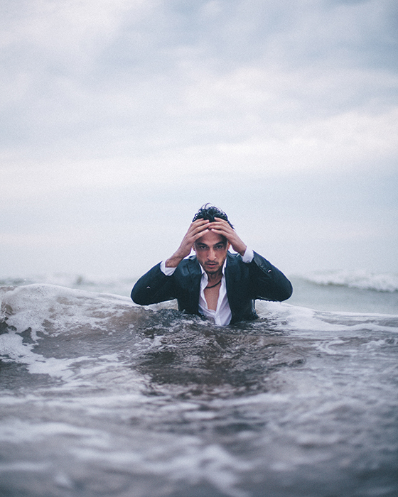A dramatic conceptual portrait of a man emerging from the sea with his hands on his head - conceptual photography ideas