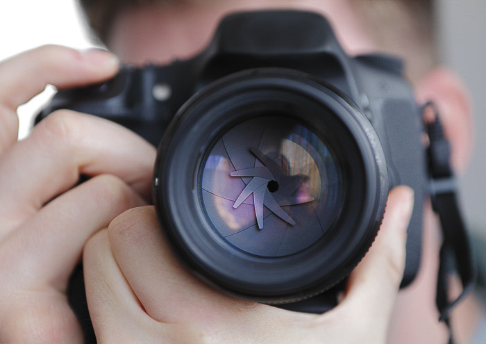 A close up of a photographer taking a shot with a DSLR to show the aperture - different camera parts
