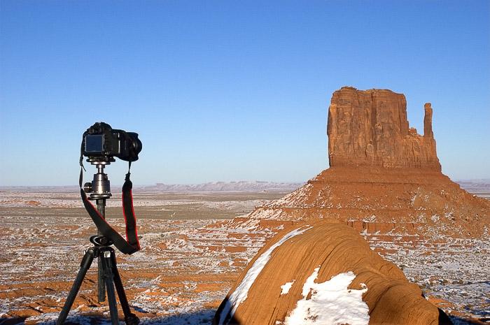 A Dslr camera set up on a tripod in a rocky landscape - different camera parts explained