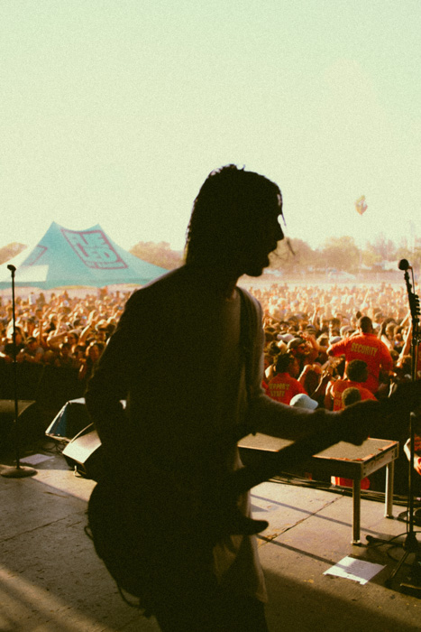 A grainy concert photography shot of a musician onstage, shot using expired film