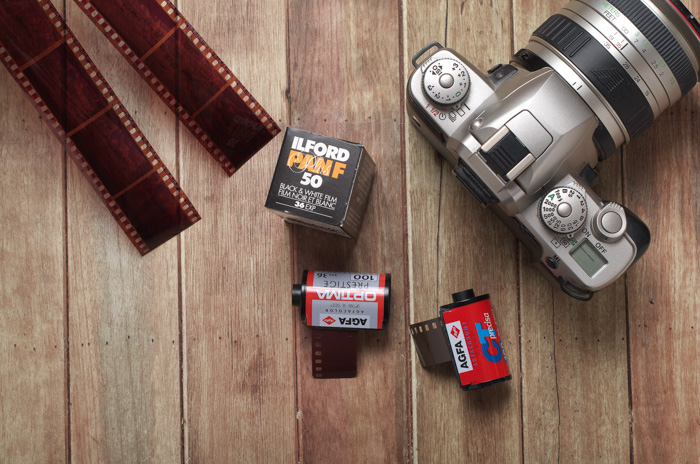 A flatlay of film rolls, negatives and film camera on a wooden table - expired film photography