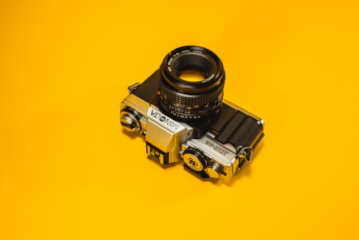 A minolta film camera on a yellow background