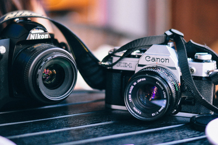 A Canon and a Nikon 35mm film camera on a table