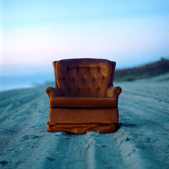 A red sofa chair taken on a beach using film photography