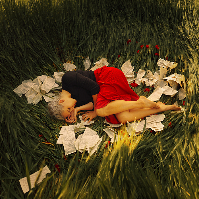 A fine art portrait of a female model curled up in grass surrounded by paper by Masha Sardari
