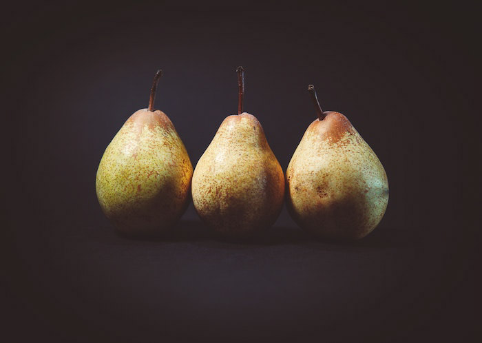 Three pears on a black background demonstrating the use of the rule of odds in food photography