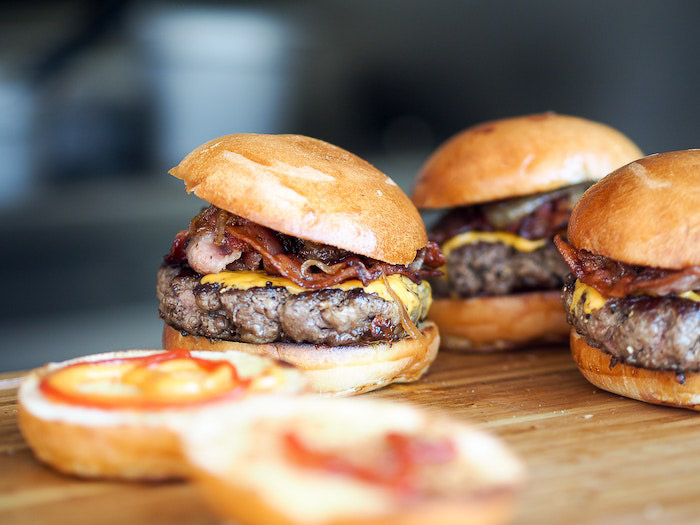A close up shot of three hamburgers on a wooden board