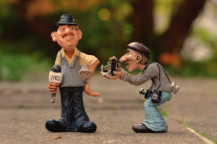 Figurines of a journalist taking a photograph of a television personality