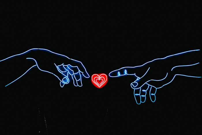 A neon sign of two hands pointing at a red love heart - best photography logo ideas
