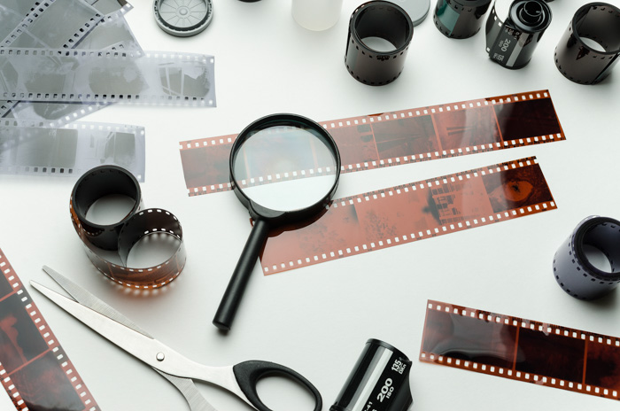A flat lay of film negatives, scissors and magnifying glass - how to develop film at home